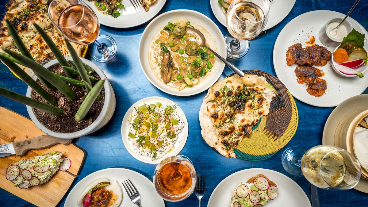 A blue table has a spread of dishes from Nix.