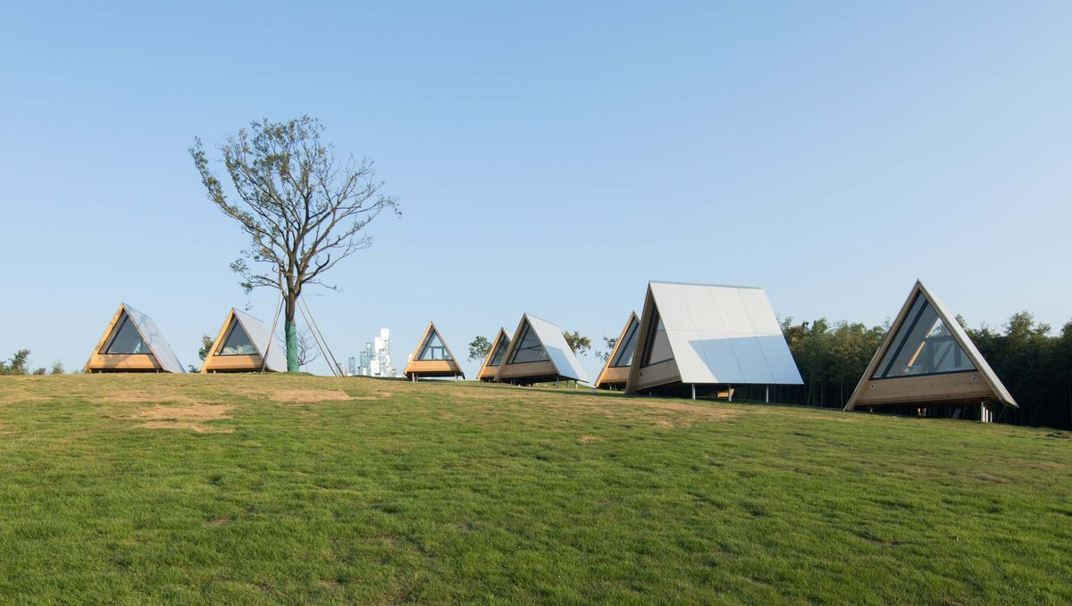 Cluster of A-frame buildings in field.