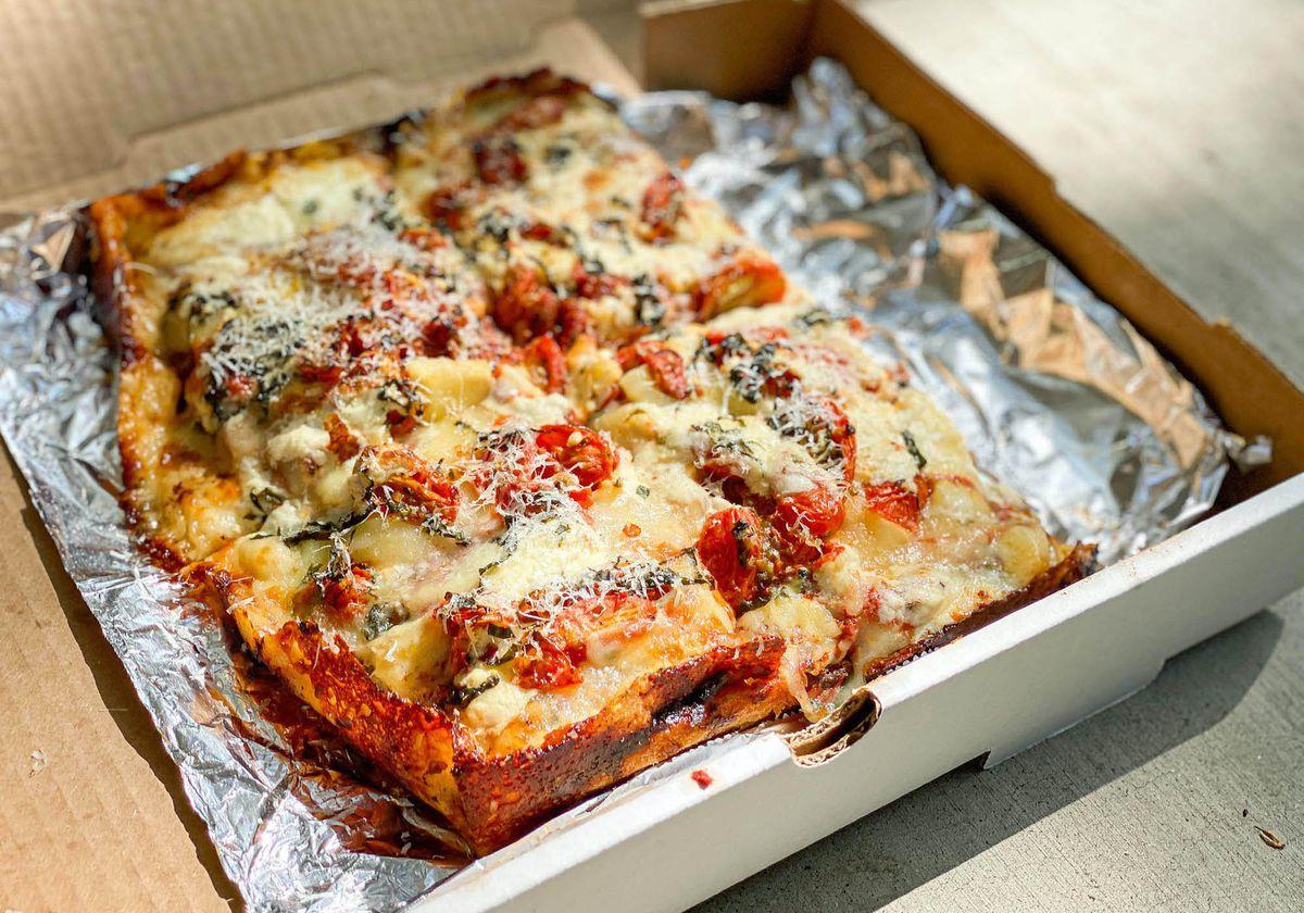 A half sheet of pan pizza with crispy cheesy edge.