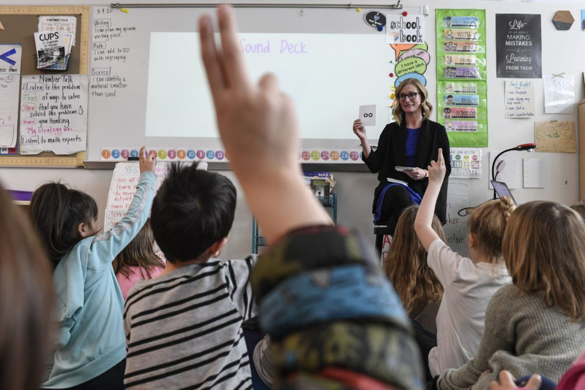 A first-grade teacher faces her students, who are seated on the rug with their backs to the camera.