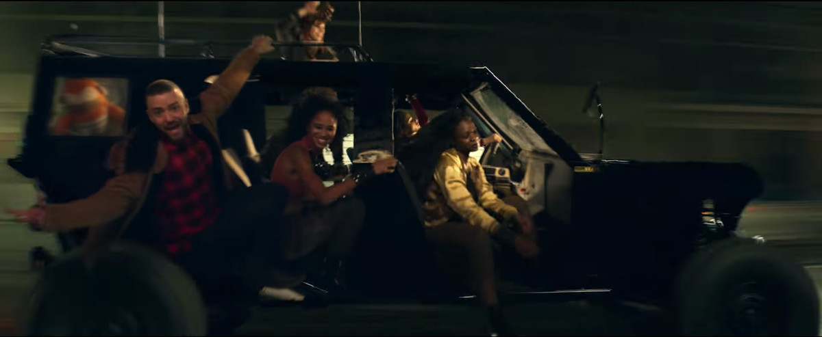 Justin Timberlake wearing red flannel in a car with two women