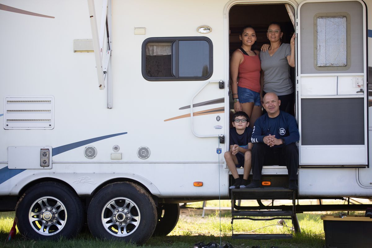 Julio Rosales, 51, photographed with his family, including Franco, 10, Doricela, 20 and Deya, 42, inside the doorframe of their RV parked in Stephenville, Texas. Julio is a juggler in a circus, but because the circuses are shut down, he is doing whatever odd jobs at fairs and carnivals that he can pick up. He's currently selling cotton candy at a carnival at a shopping center.