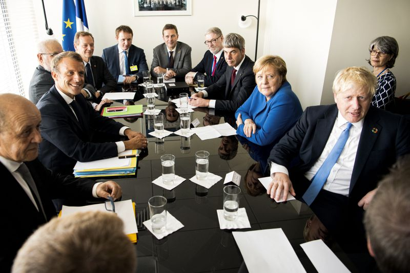 German Chancellor Angela Merkel, UK Prime Minister Boris Johnson, and French President Emmanuel Macron sit with others around a meeting table at the UN Climate Summit.