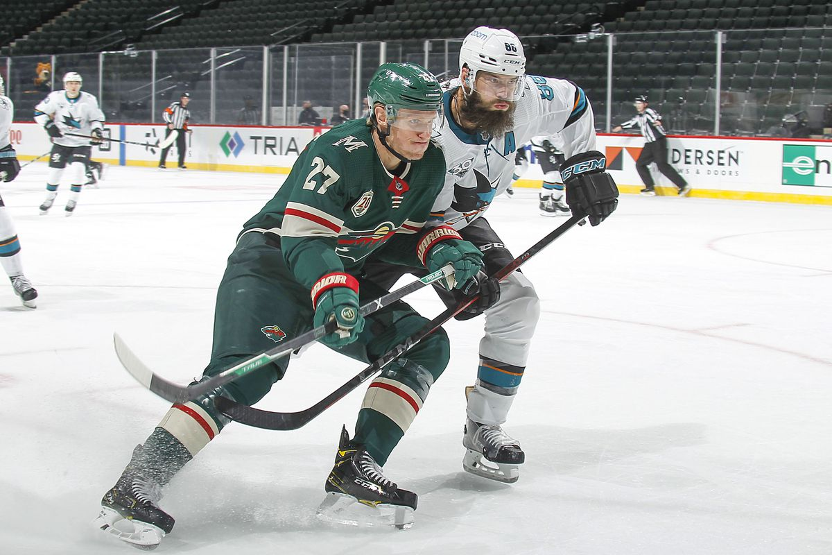 Nick Bjugstad #27 of the Minnesota Wild and Brent Burns #88 of the San Jose Sharks skate to the puck during the game at the Xcel Energy Center on January 22, 2021 in Saint Paul, Minnesota.