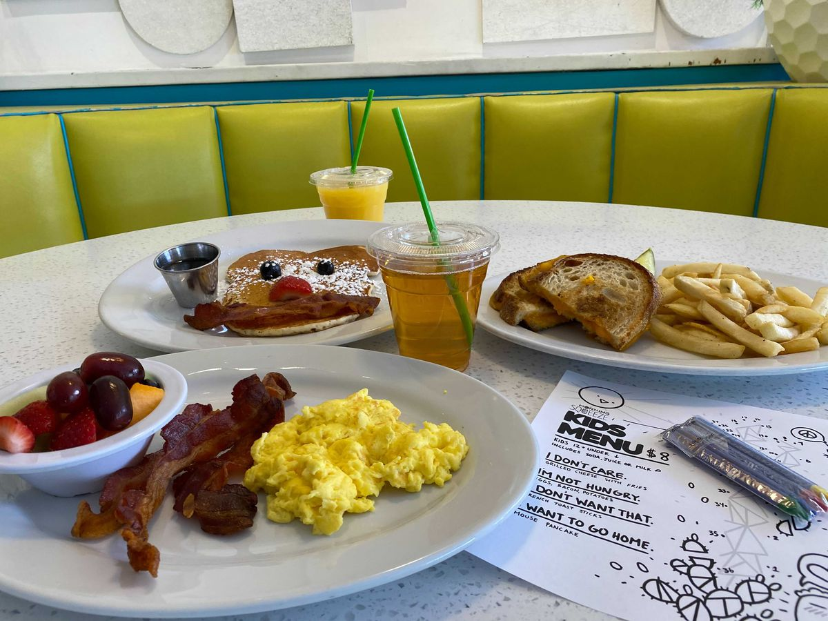 A booth with bright green upholstery and plates of pancakes, sandwiches, bacon, and eggs on a table next to a coloring page.