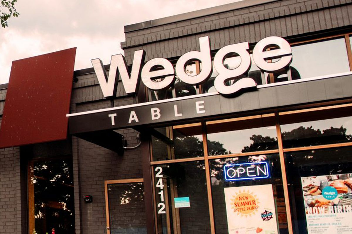 The exterior of The Wedge Table with a large white letters spelling out Wedge and the word table smaller underneath. The new-construction-style modern building has black/gray fixtures and large panel glass windows