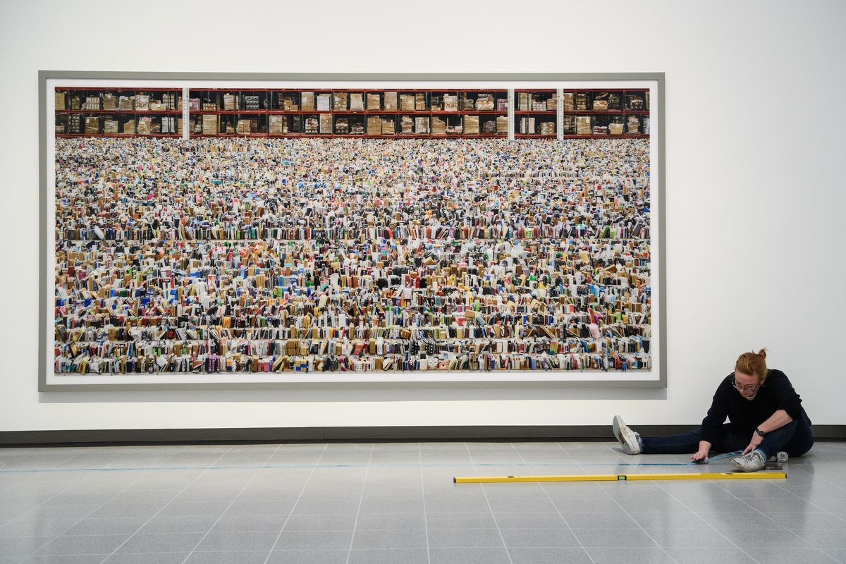 """A woman works sitting on the floor of a gallery in front of a large-scale photograph entitled """"Amazon."""""""