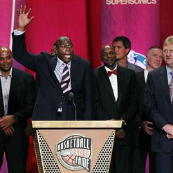 """Basketball Hall of Fame inductees, members of the 1992 U.S. Olympics """"Dream Team,"""" look on as Magic Johnson speaks during enshrinement ceremonies in Springfield, Mass., Friday. In back are Charles Barkley, Clyde Drexler, Christian Laettner, Chris Mullin and Larry Bird."""