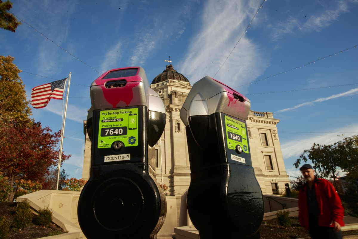 Pink paint still partially covers the parking meters at the...