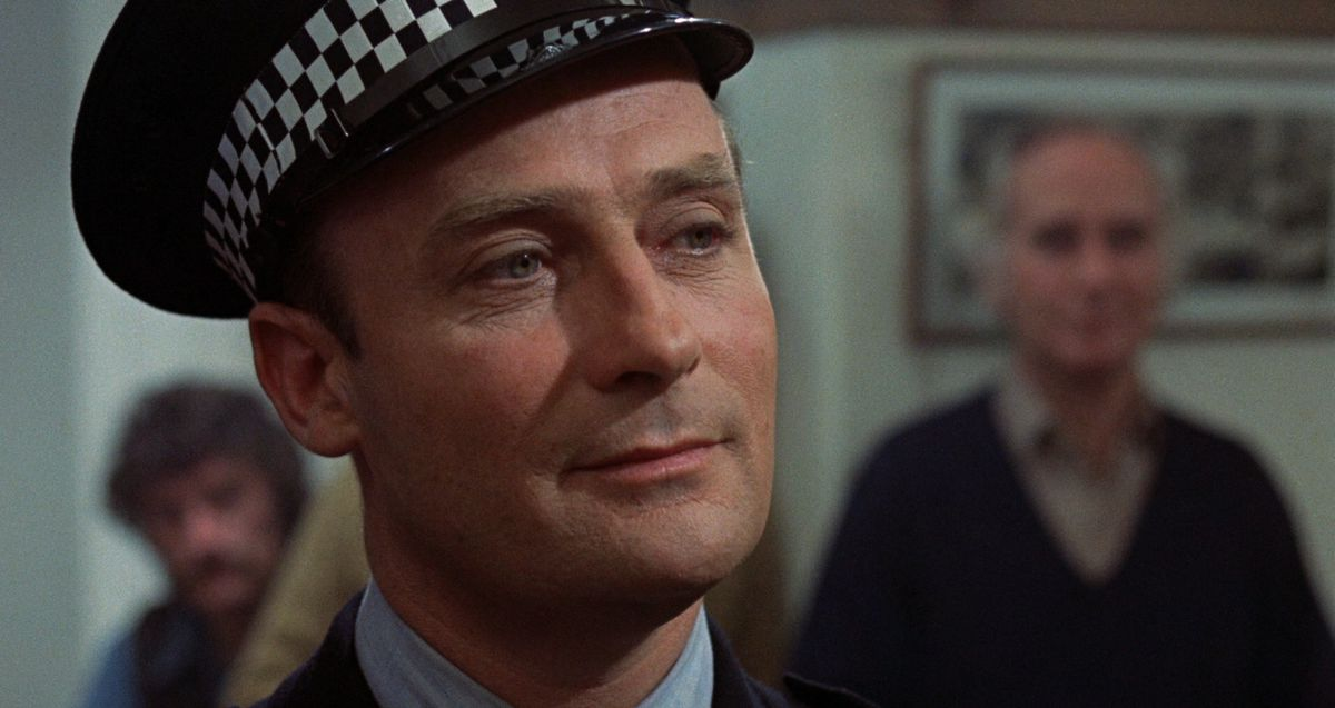 Sgt. Neil Howie (actor Edward Woodward) in close up, smiling