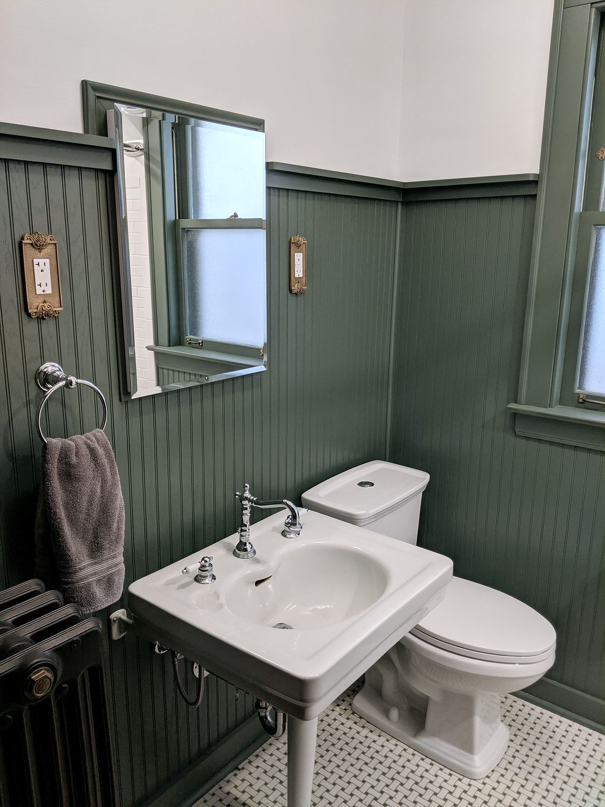 A bathroom with green wainscotting, white and green cross-hatched tile, a pedestal sink and a toilet.
