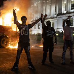 Protesters pose in front of a burning truck outside the Kenosha County Courthouse, where police clashed with protesters in the second night of unrest after police shot Jacob Blake in the Wisconsin city, Monday night, Aug. 24, 2020.