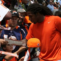 Denver Broncos safety David Bruton takes time to sign autographs after practice Wednesday.