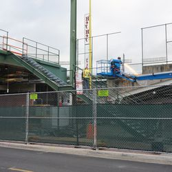 Chain link fence at the end of the third base line grandstands being cut away, next to the left field foul pole