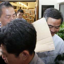 Hong Kong Chief Executive Leung Chun-ying, right, is hit by a protester's placard at a polling station for the Legislative Council election in Hong Kong, Sunday, Sept. 9, 2012. Hong Kong voters cast their ballots Sunday in legislative council elections that will see them choosing more than half the seats for the first time. Voters are selecting 40 representatives while 30 others are chosen by business and special interest groups. In previous votes, it was evenly split but 10 new seats have been added this time.