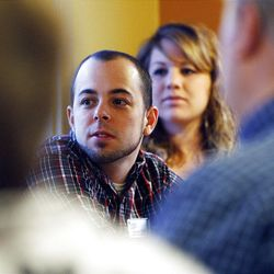 Quynn Udell, a delegate, and his wife, Chelsea, listen to candidate Carl Wimmer at IHOP.