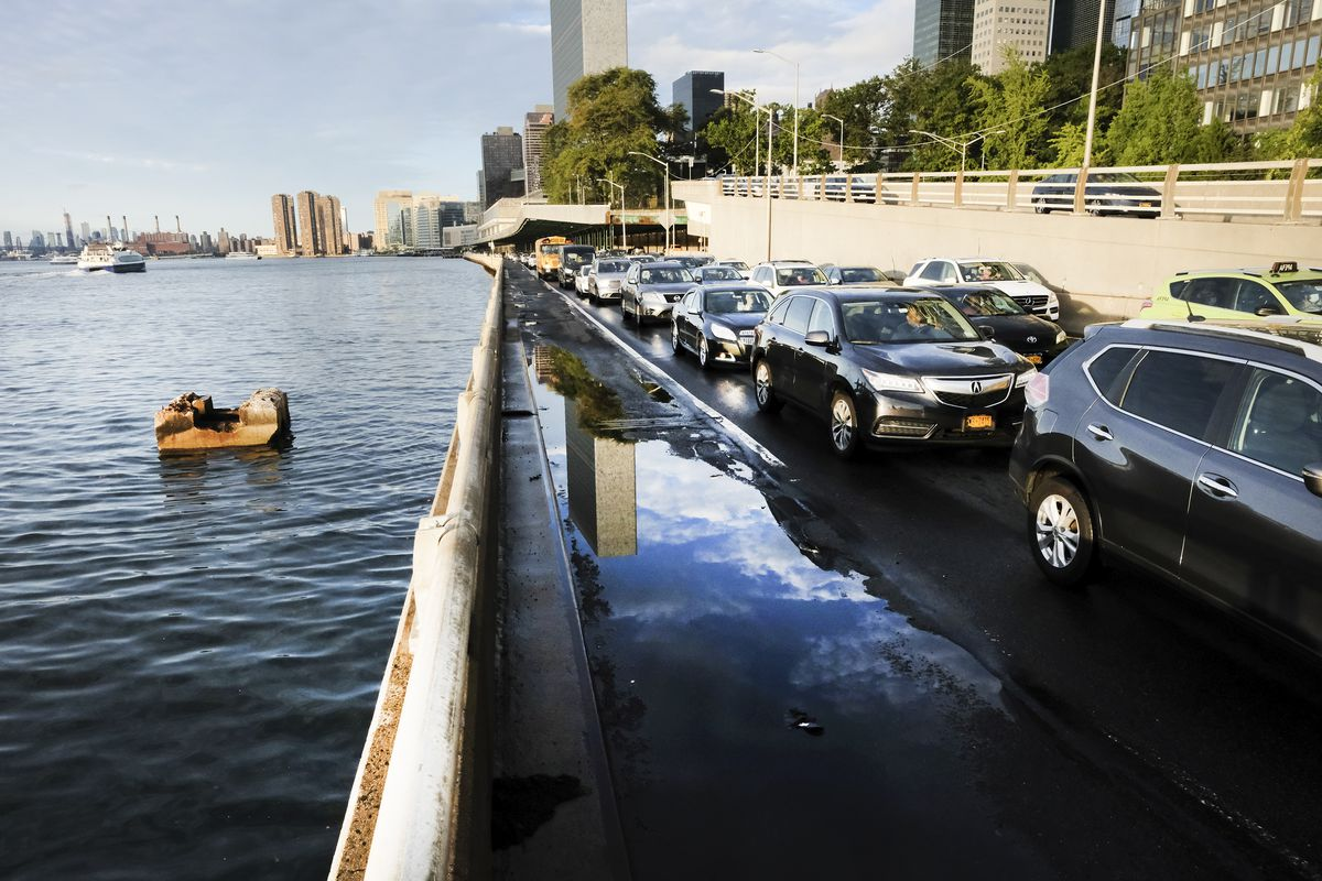 Cars sitting in traffic on a roadway beside a harbor.