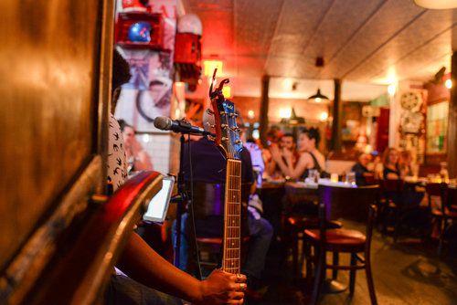 A musician holds a guitar inside Maison Harlem