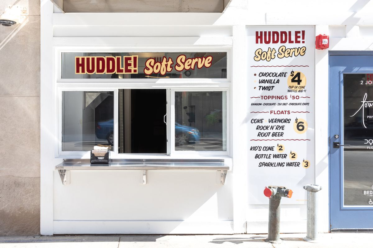 a white walk-up window for Huddle with red and yellow signs and menus