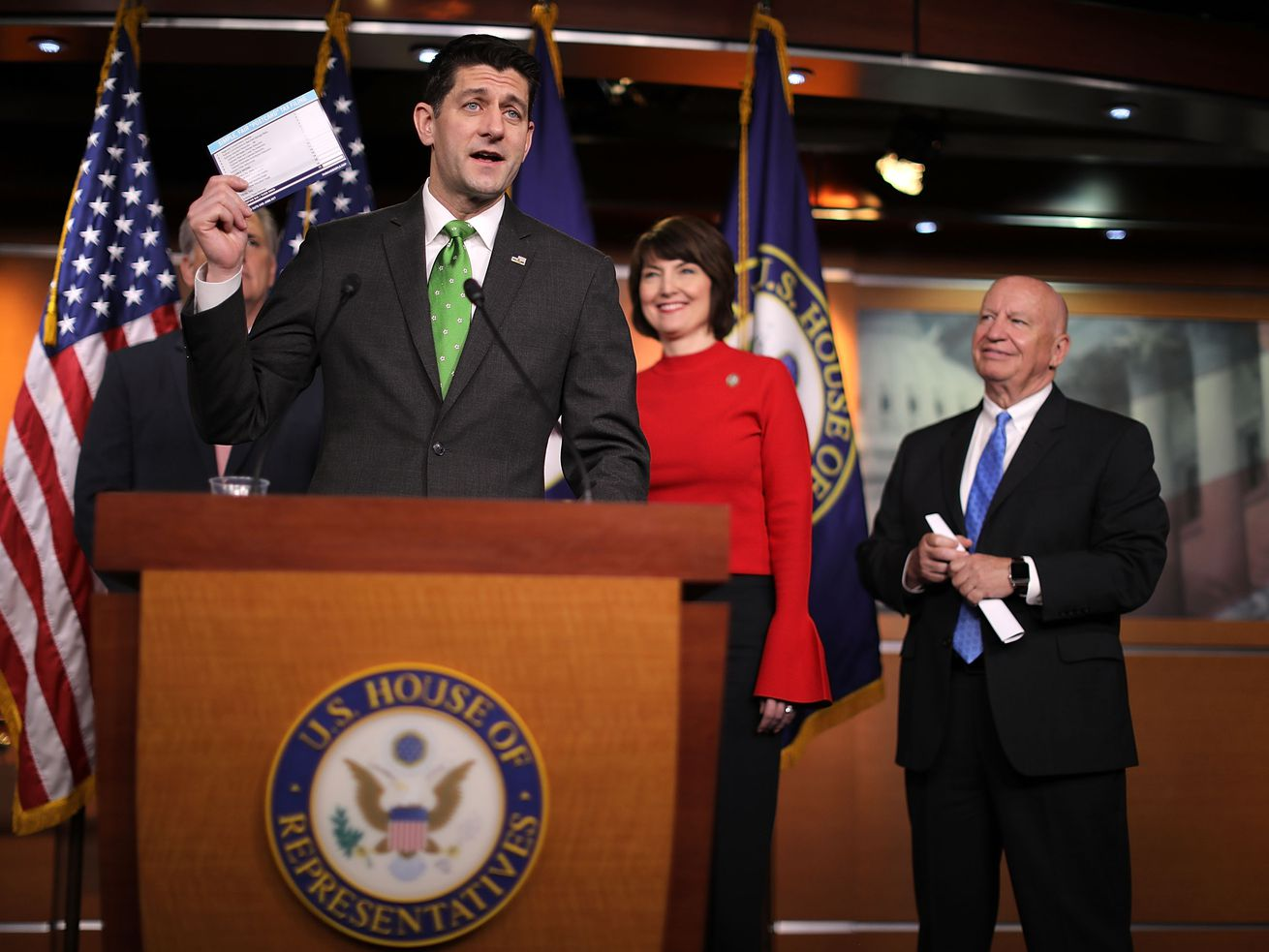 Speaker of the House Paul Ryan holds up an example of a proposed tax form at a press conference in April 2018.
