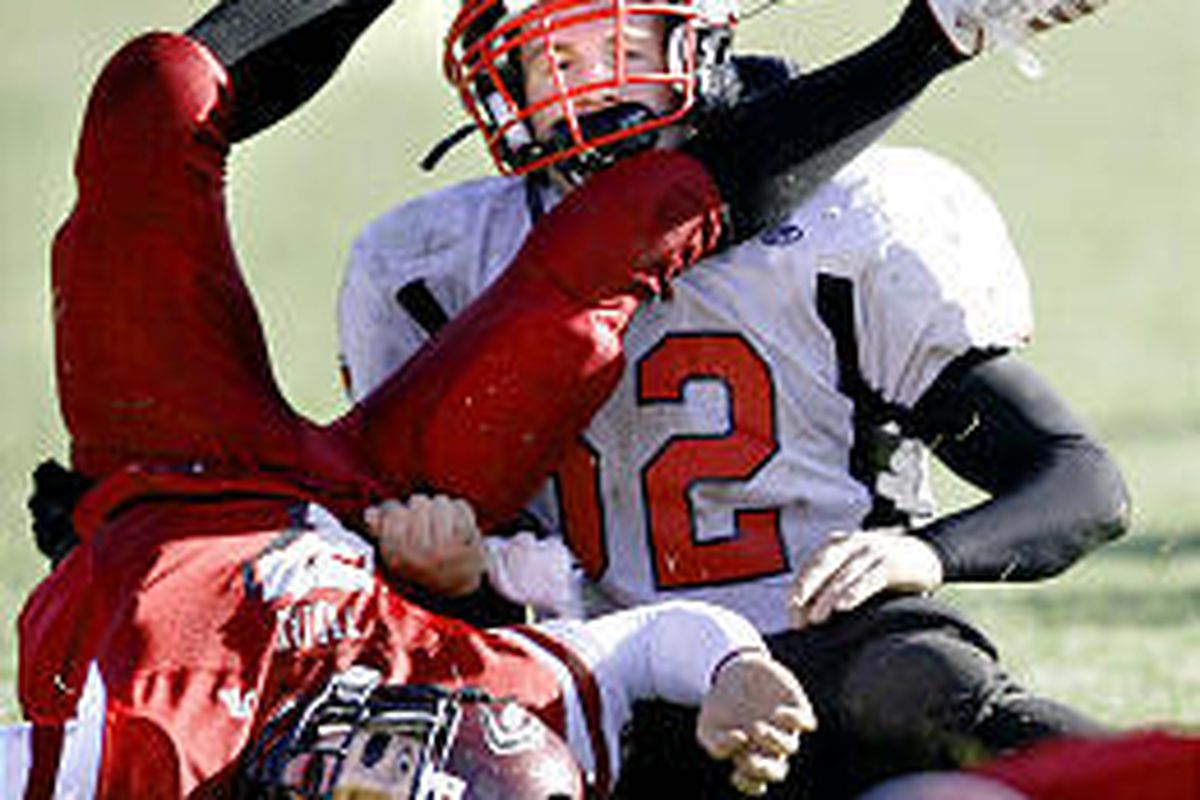 Grantsville's Micah Watson (in white) and Morgan quarterback Alan Tucker get tangled up after Watson knocked the ball loose for a fumble in 3A state quarterfinal action Saturday.