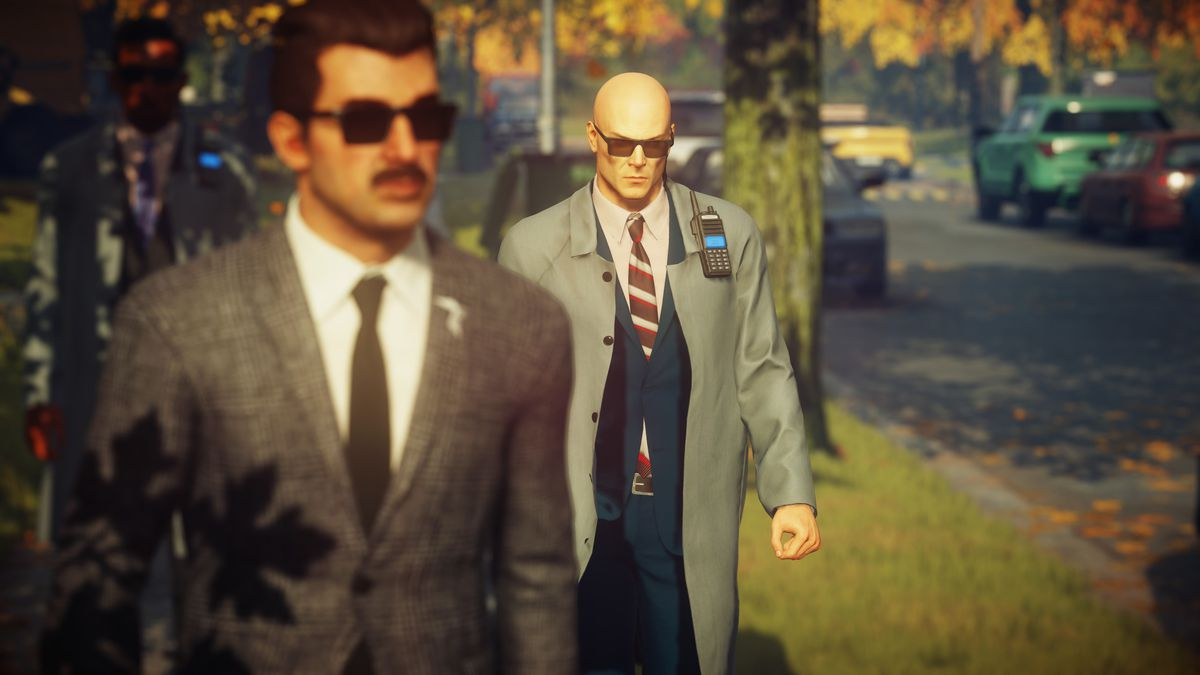 A bald assassin in a suit and trench coat follows his target in Hitman 2