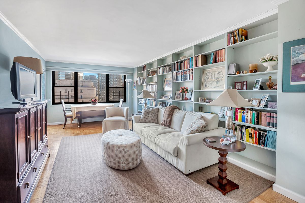 A living room with light blue walls, built-in bookshelves, a beige couch, a TV on a wooden stand, and large windows.