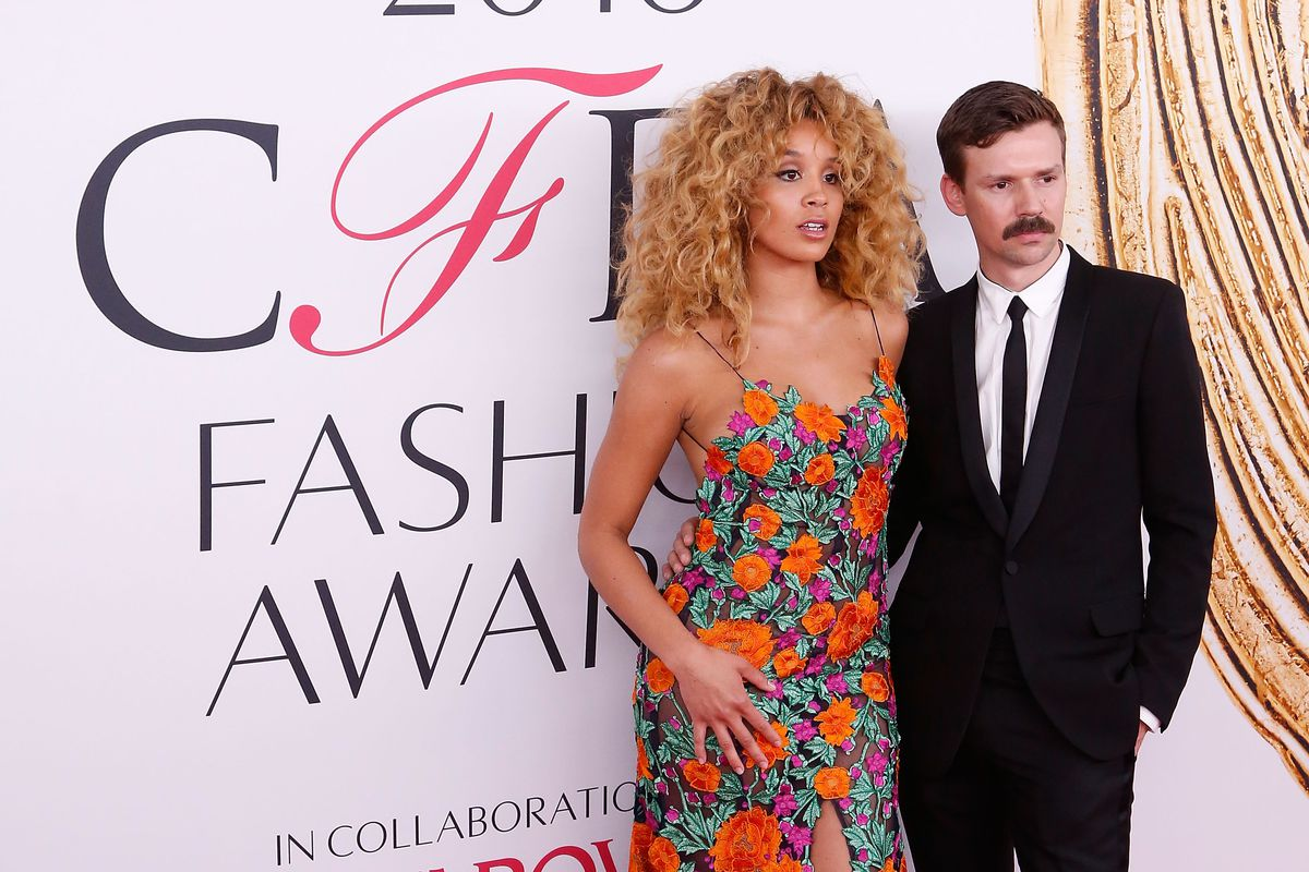 Jilliam Hervey wears an orange, green, and purple floral Adam Selman dress on the red carpet of the CFDA Fashion Awards. Selman wears a suit.