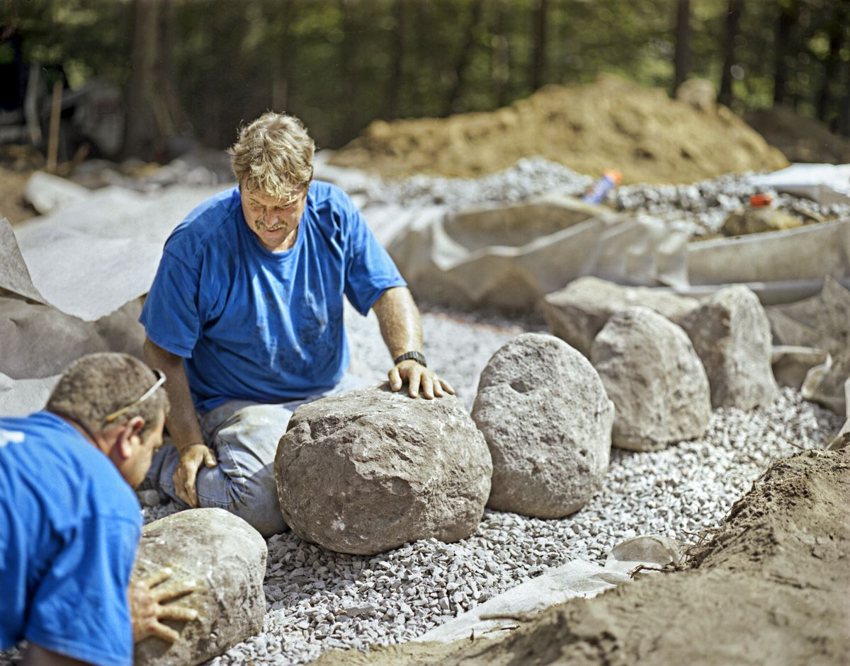 Men Lay First Course Of Stones Of Freestanding Stone Wall