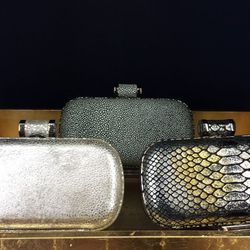 (from left) <b>Halston Heritage</b> Silver Spark clutch, $40; Halston Heritage Gravel Clutch, $40; Halston Heritage Bronze Snake clutch, $40