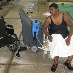 """Karen Kitchen prepares to move back to her wheelchair after using a poolside chair lift to raise her from the water at the Chatham County Aquatic Center on Tuesday, April 17, 2012, in Savannah, Ga. Kitchen has multiple sclerosis and says the indoor pool is one of the few in Savannah with a lift for people with disabilities. """"I couldn't get into the pool otherwise,"""" she said. Hotels, municipal recreation centers and other swimming pool operators are scrambling to comply with new government regulations requiring public pools to be accessible to people with disabilities."""