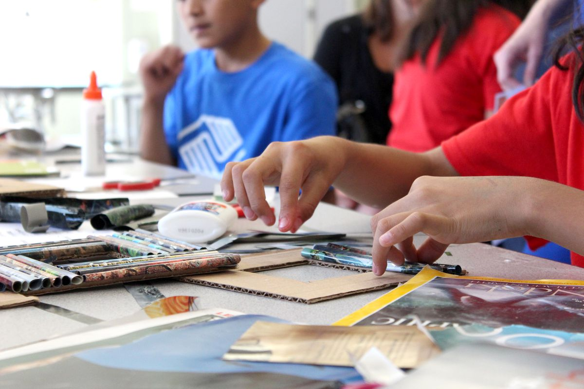 """A student glues rolled up magazine pages onto a picture frame. The activity, offered by the Boys & Girls club, was all about creating """"up-cyclced"""" art."""