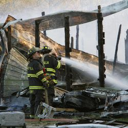 Lake Villa firefighters work to extinguish a fire at Black Tie Stable in McHenry, Ill., Wednesday, April 11, 2012. The five alarm fire destroyed the facility and killed 10 horses. Fire companies from throughout the area were on hand to help.