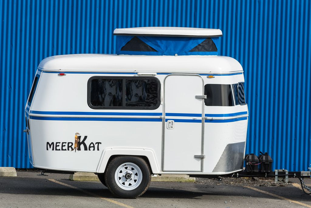 A small white trailer with two blue stripes. There is a word on the side of the trailer: Meerkat.