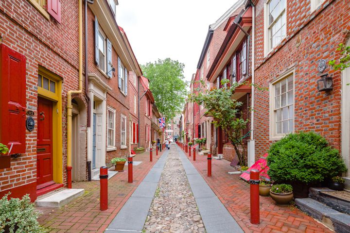 An alley in Philadelphia. On both sides of the alley are buildings with red brick facades and colorful doors.
