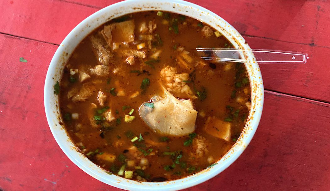 An overhead shot of a bowl of red menudo.