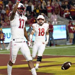 Utah wide receiver Devaughn Vele (17) celebrates his touchdown catch with Britain Covey (18) during the first half of the team's NCAA college football game against Southern California on Saturday, Oct. 9, 2021, in Los Angeles.