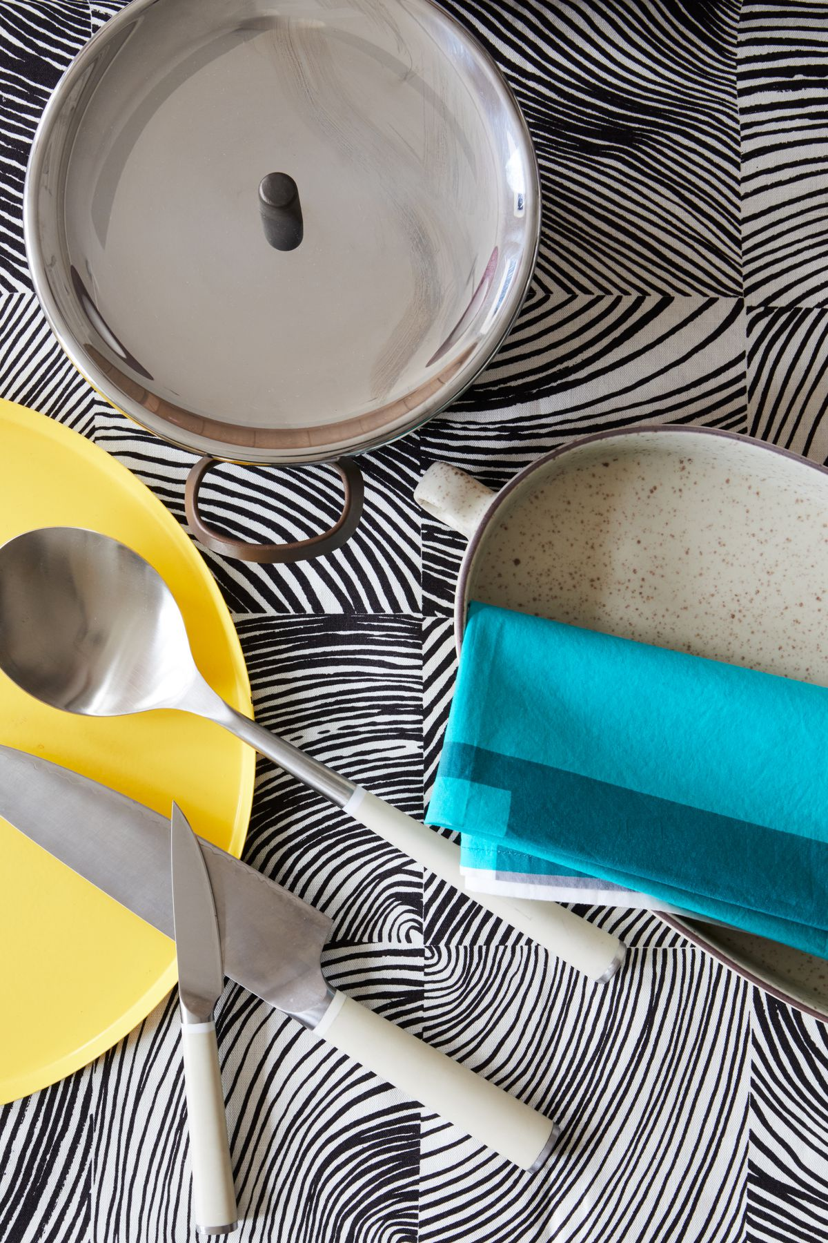 Cookware and utensils on a surface with a black and white abstract pattern.