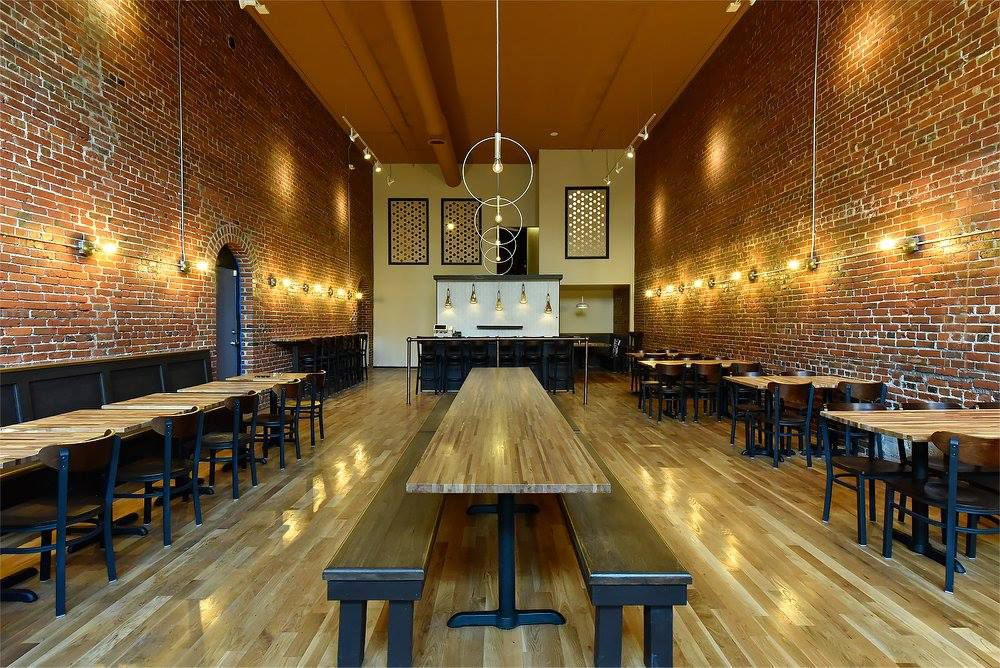The expansive dining room at Nirmal's, with a large wooden communal table in the center