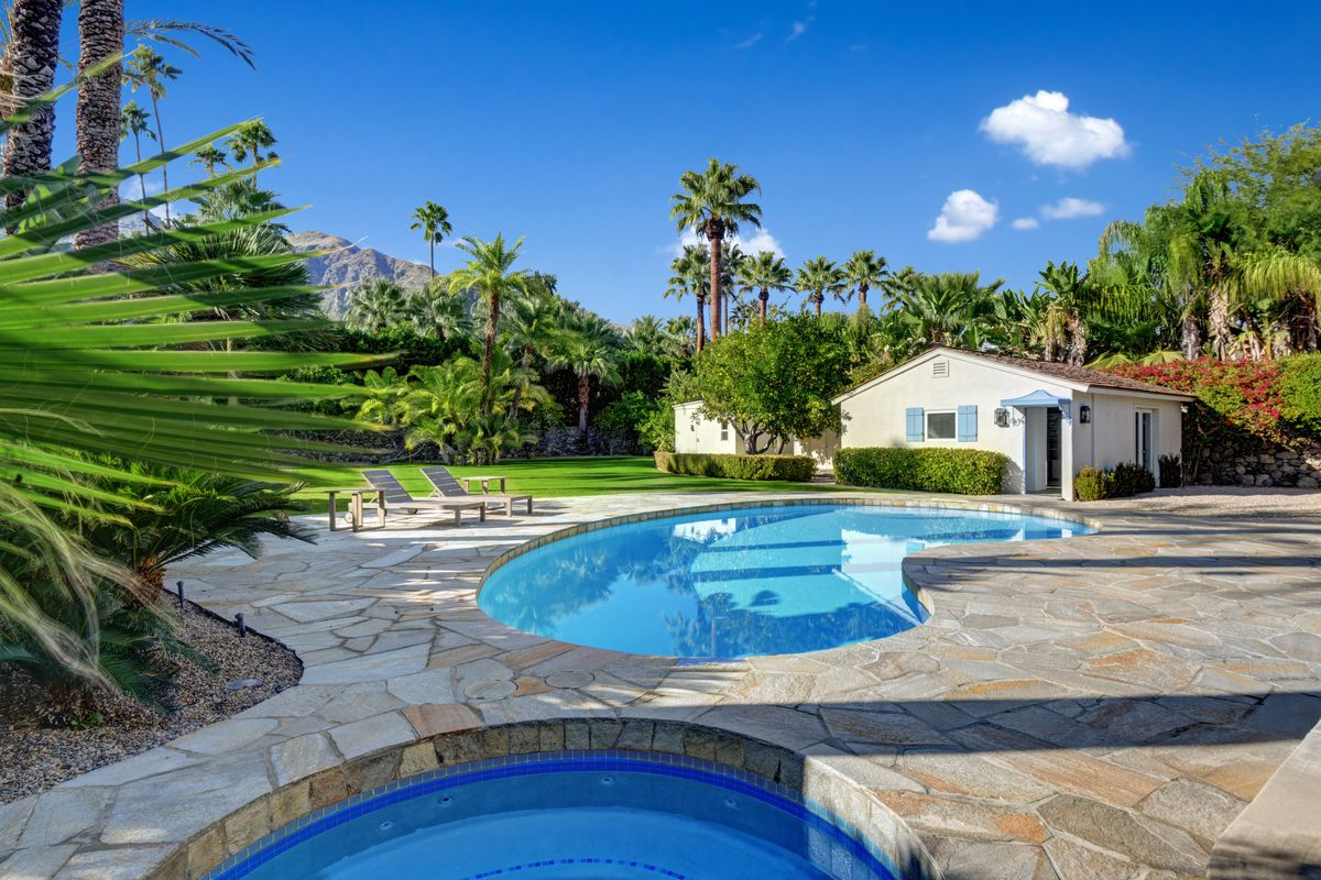 A view of a stone patio with a spa and pool. A small white and blue casita sits behind the pool.