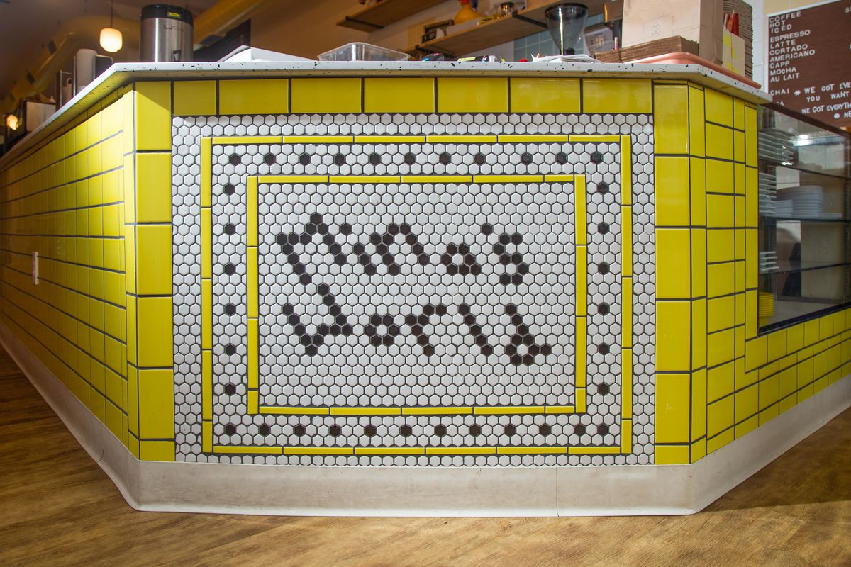 the interior counter of mina's world with yellow tiles and white and black tiles that say mina's world