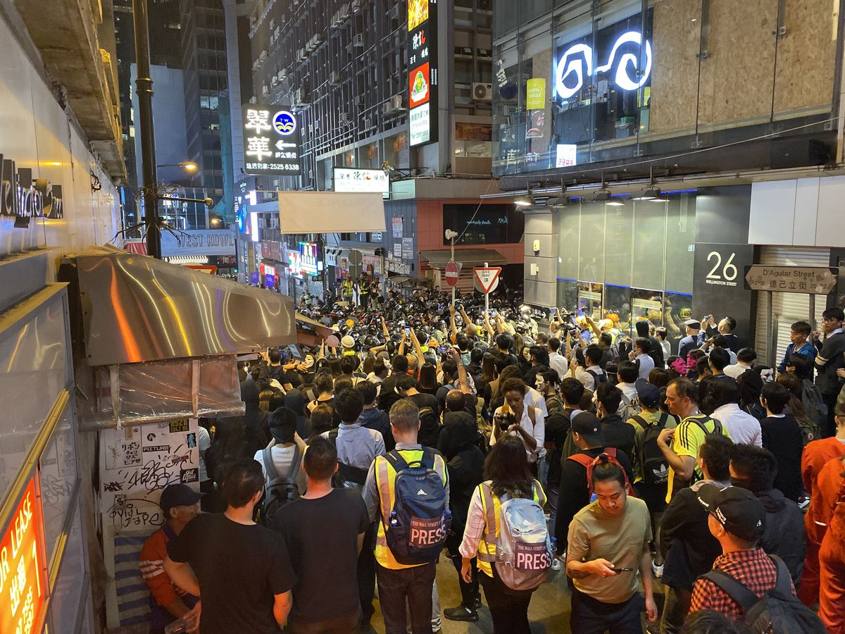 Crowds fill the streets in front of a police line