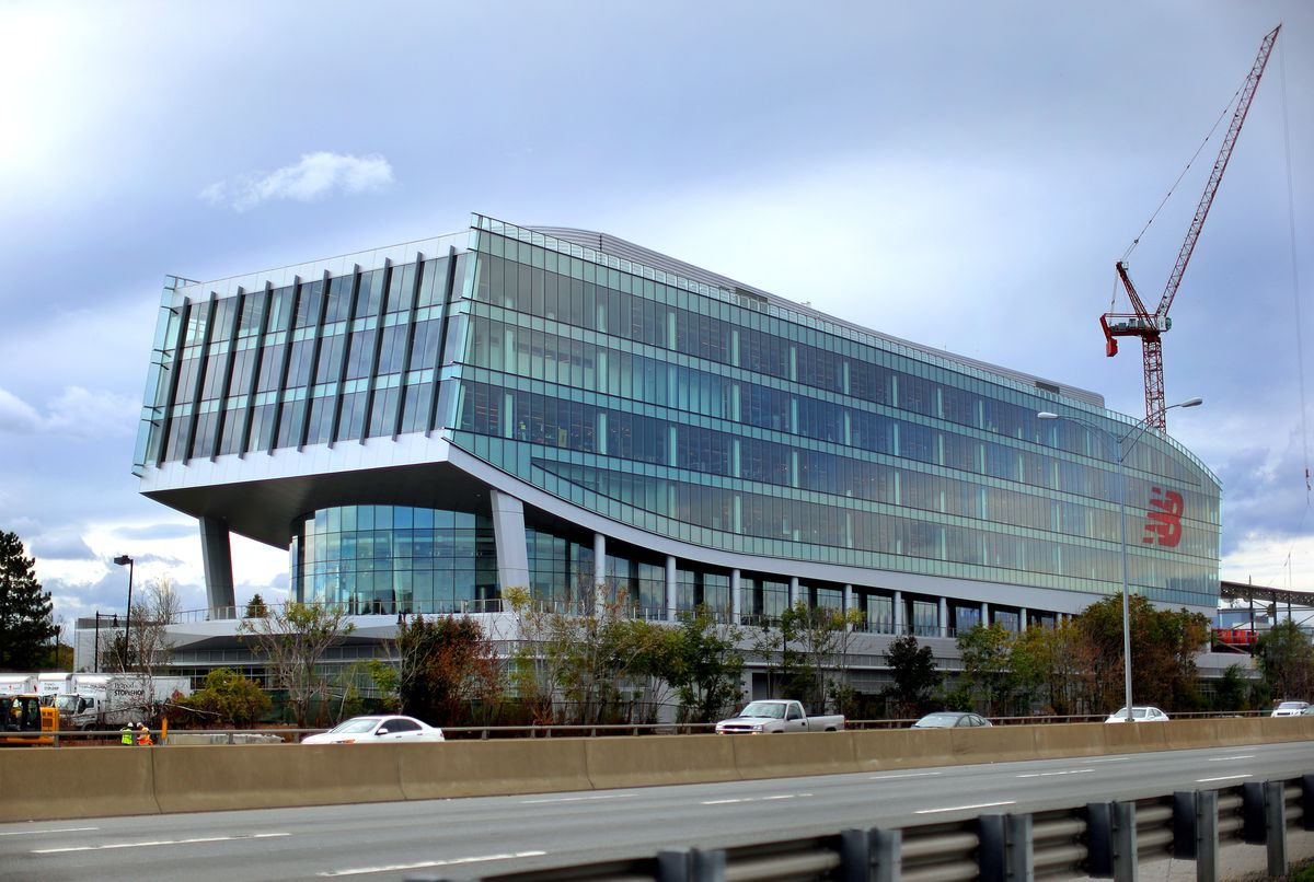A long, large, rectangular-like building with a glass exterior by the side of a highway.