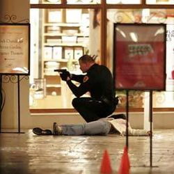 A Salt Lake City police officer squats, his gun drawn, next to a shooting victim inside the Trolley Square Mall, Monday night. Six people, including the gunman, died from the shooting.