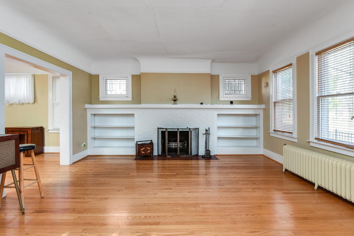 A big living room with a brick fireplace straddled by two built-in white shelves. A low yellow-painted radiator is under the windows.