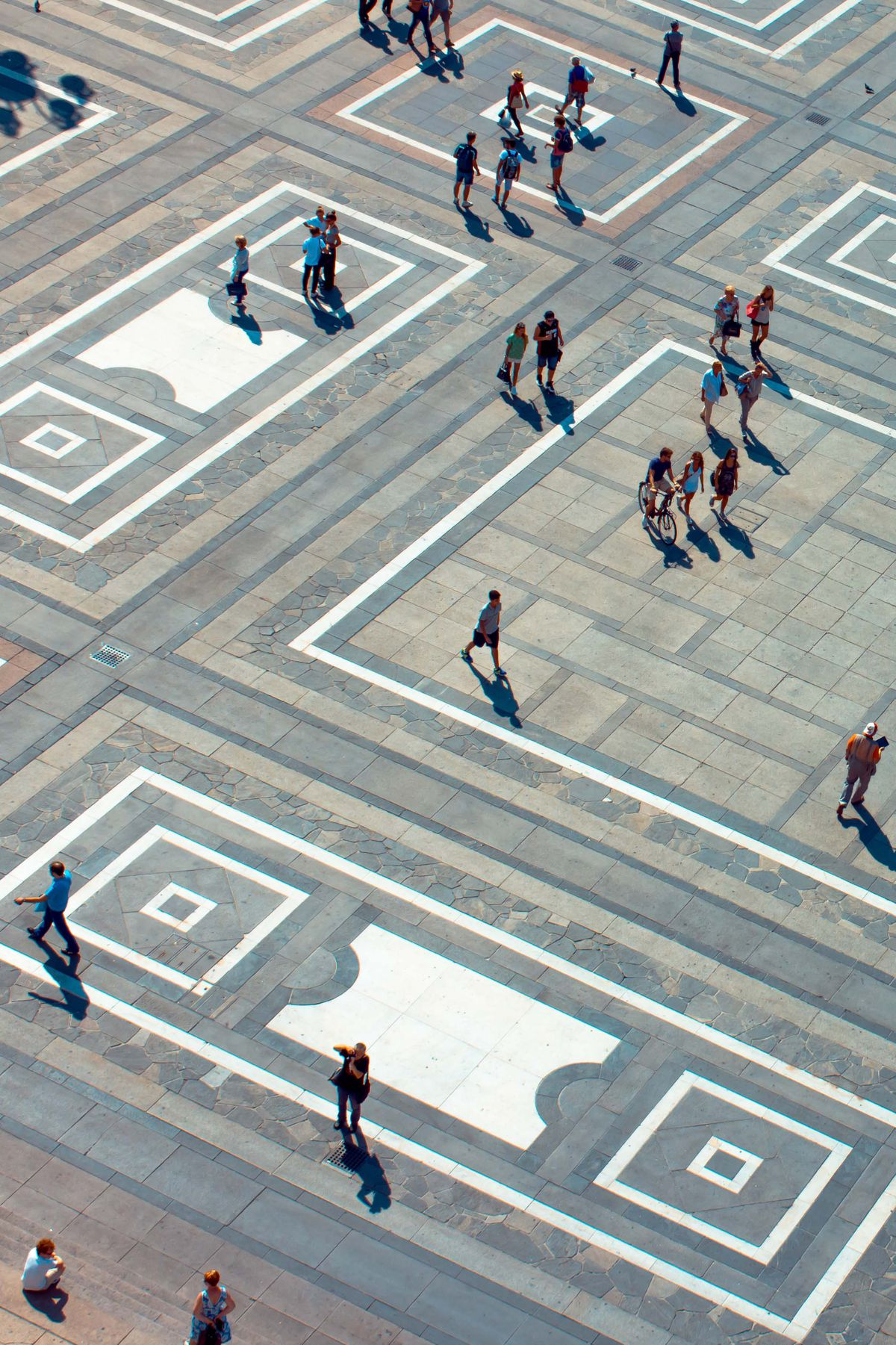 An aerial view of a pedestrian plaza. The ground has a pattern and there are people walking on the plaza.