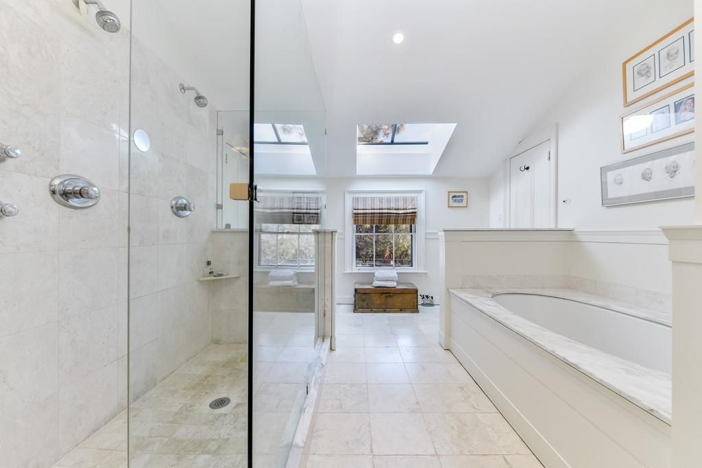 A large, long bathroom with a glass-enclosed shower next to a soaking tub.
