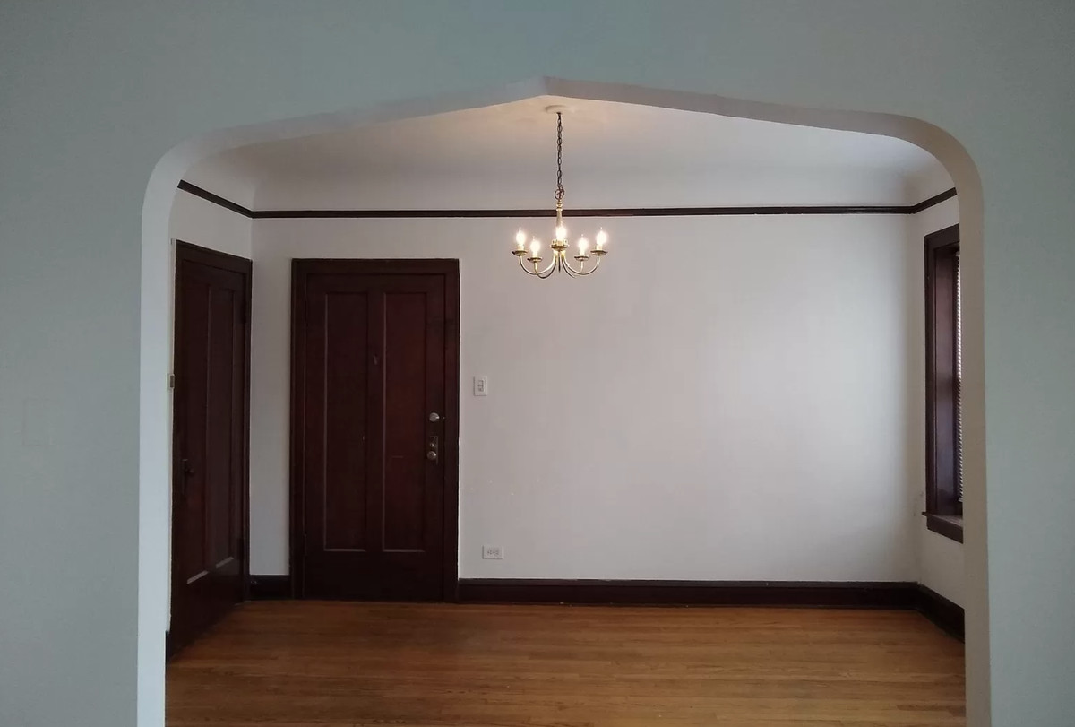 A view into the living room with a little gold light fixture and dark wooden doors.