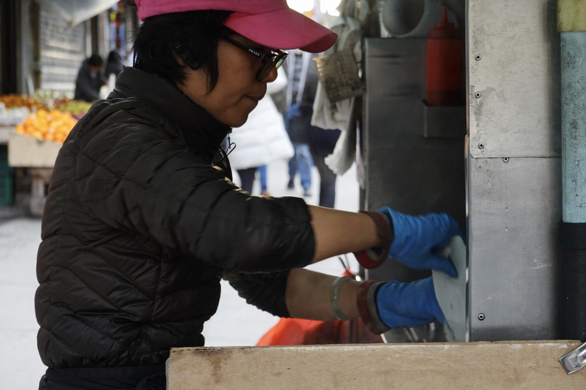 A woman wearing glasses, a neon pink baseball cap and blue gloves, works at a street food cart