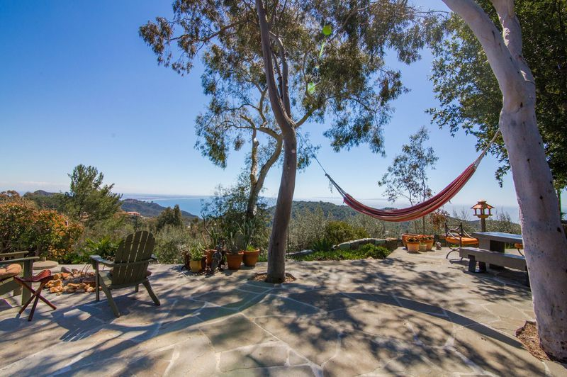 Outdoor stone patio with mountain and ocean views. A hammock hangs between two trees.